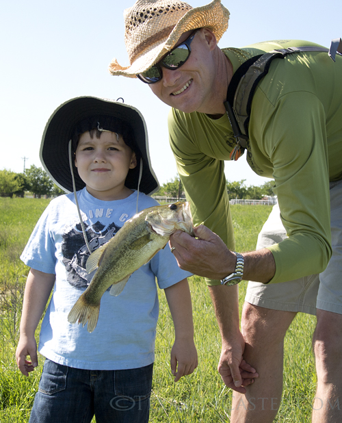 A happy pond fisher with a largemouth bass.